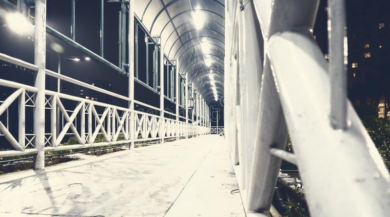 明亮的白色步行桥在晚上 免版税库存照片