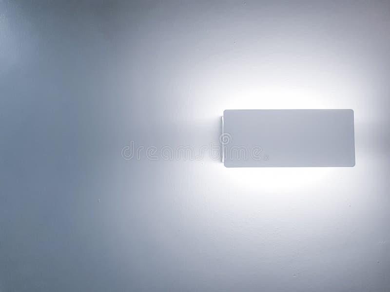明亮的白色灯发光在墙壁的-在白色背景隔绝的最低纲领派壁灯装置 免版税库存图片