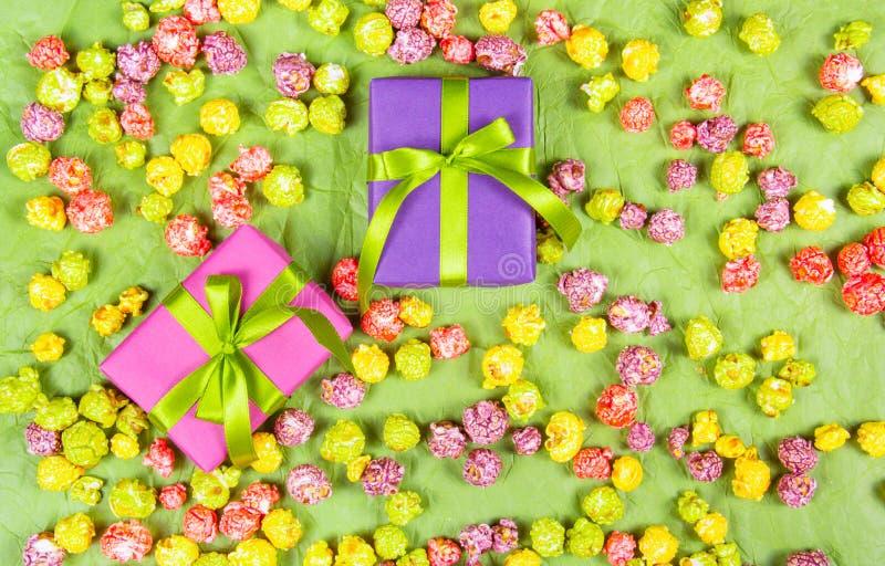明亮的礼物盒和色的焦糖玉米花 假日背景和纹理 免版税库存照片