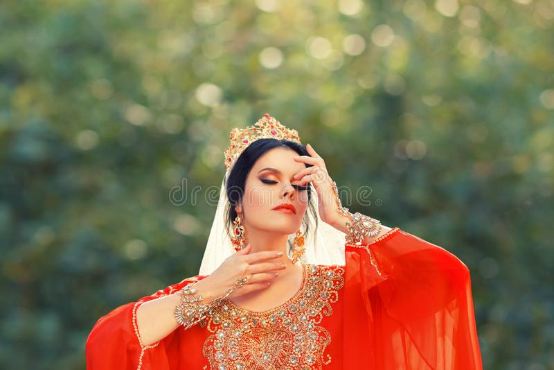 明亮的红色猩红色光礼服的迷人的令人愉快的土耳其夫人投入她的手对一张华美的面孔,女主人Roksolana 免版税库存照片