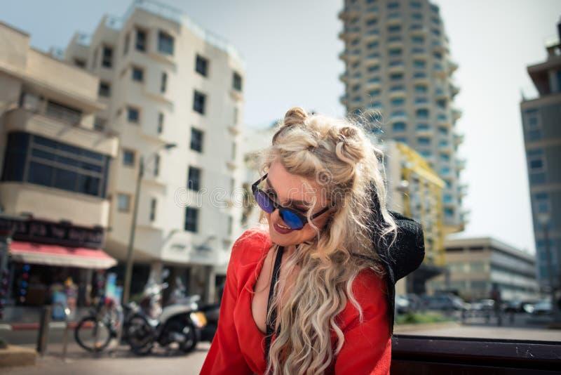明亮的红色礼服的年轻可爱的妇女坐长凳 免版税库存照片