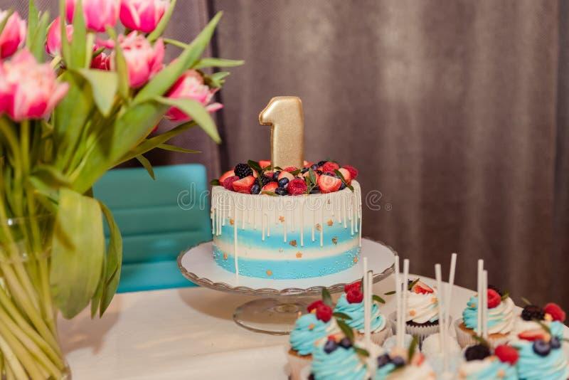 明亮的绿松石婴孩生日蛋糕和棒棒糖一个年党 室内装饰为一个孩子儿童生日是一个 免版税库存照片