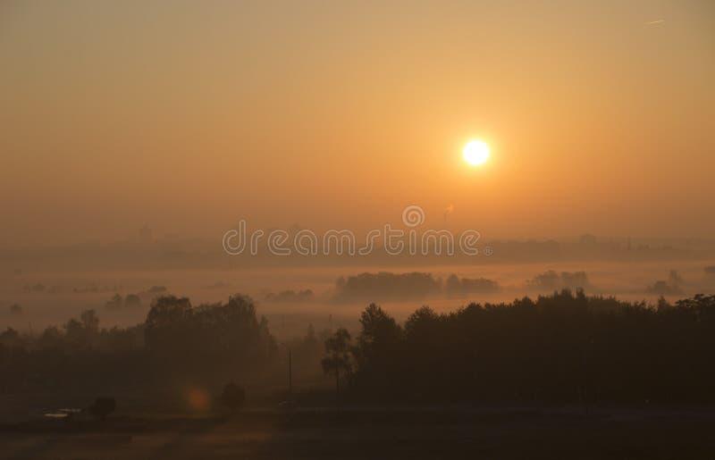 明亮的美好的黎明,太阳上升在城市,光穿过雾 库存照片