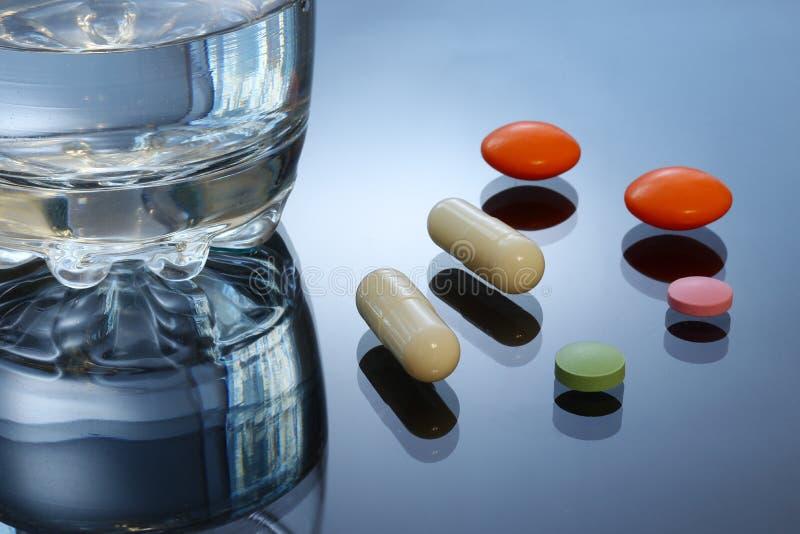 明亮的色的片剂,药片,在玻璃桌上的胶囊 库存图片