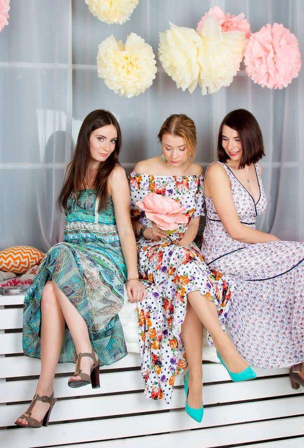明亮的色的礼服的三个年轻美丽的女孩 Decoratio 图库摄影