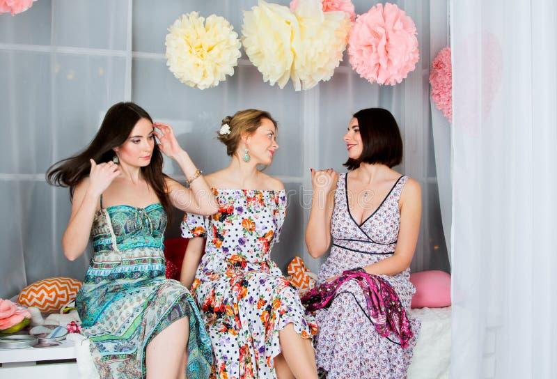 明亮的色的礼服的三个年轻,美丽和情感女孩 免版税库存图片