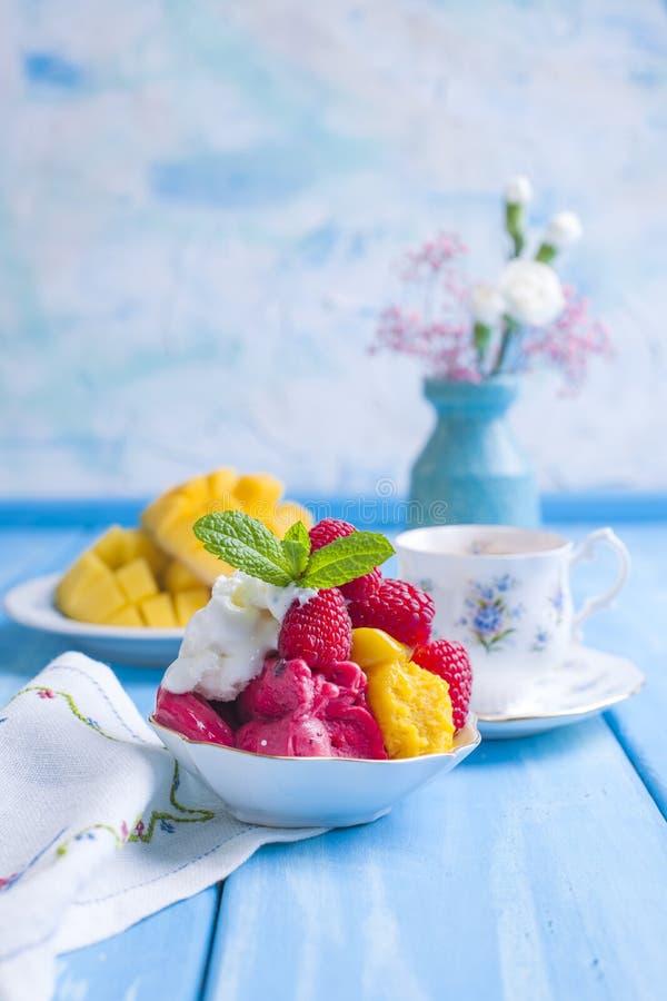 明亮的花冰淇凌用莓和薄菏在一块板材,在蓝色木背景 一个杯子早晨咖啡和光 库存图片