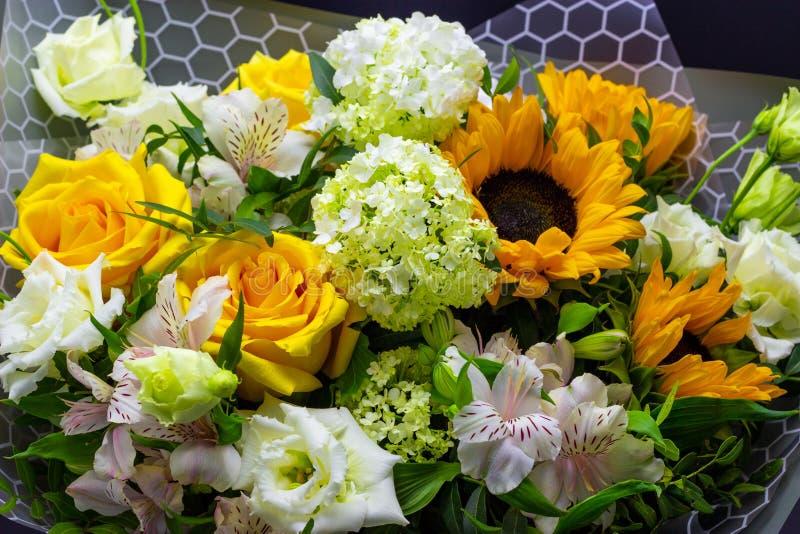 明亮的花束用黄色向日葵和玫瑰、桃红色南北美洲香草和绿色荚莲属的植物花卉背景 免版税库存照片