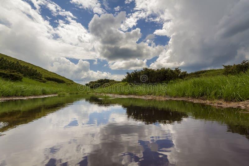 明亮的蓝天美好的平安的夏天视图与点燃的由在山湖赌注清楚的水反映的太阳白色松的云彩  库存照片