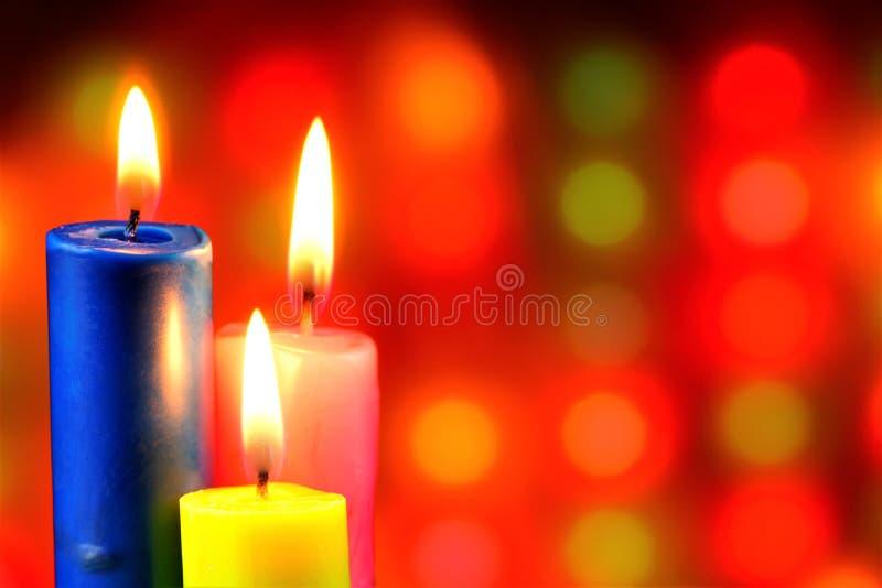 明亮的蜡烛在欢乐圣诞灯背景烧  信念、希望和生活的蜡烛标志 库存照片