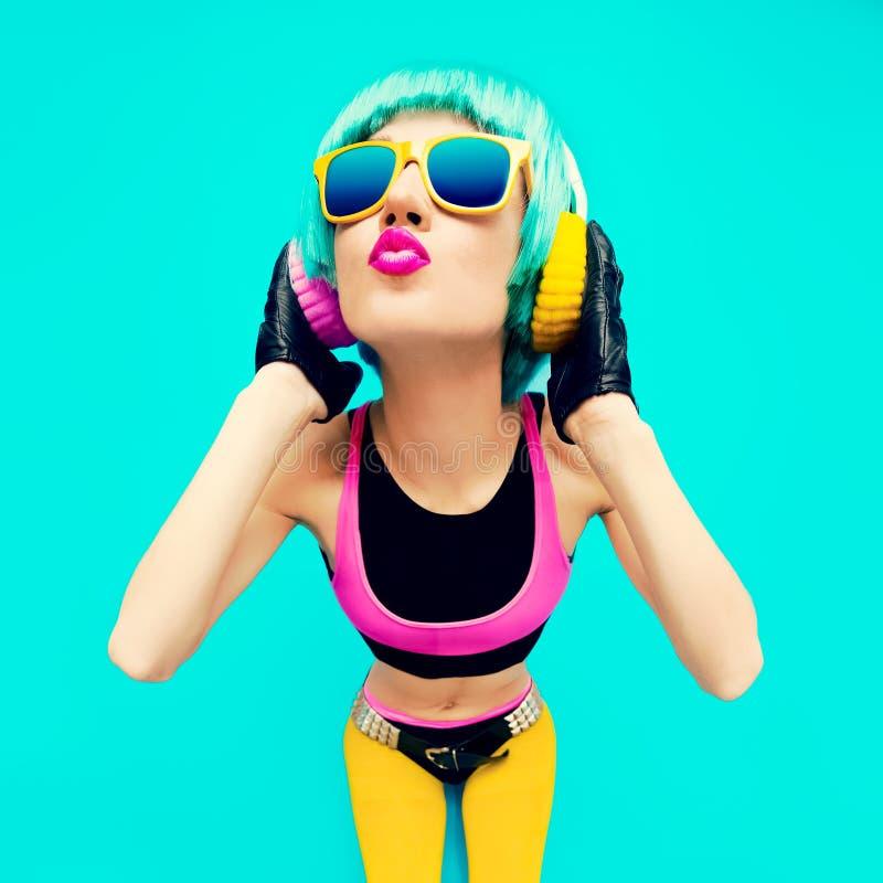 明亮的衣裳的迷人的时尚DJ女孩在蓝色背景 免版税图库摄影