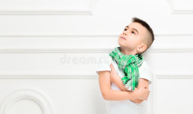 明亮的裤子的时尚美丽的小男孩和T恤杉和围巾 免版税库存照片