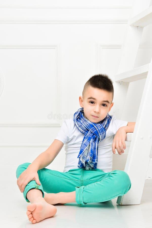 明亮的裤子的时尚美丽的小男孩和T恤杉和围巾 免版税库存图片