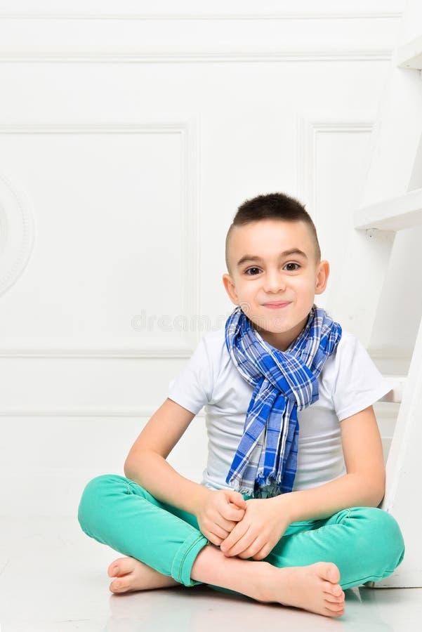 明亮的裤子的时尚美丽的小男孩和T恤杉和围巾 图库摄影