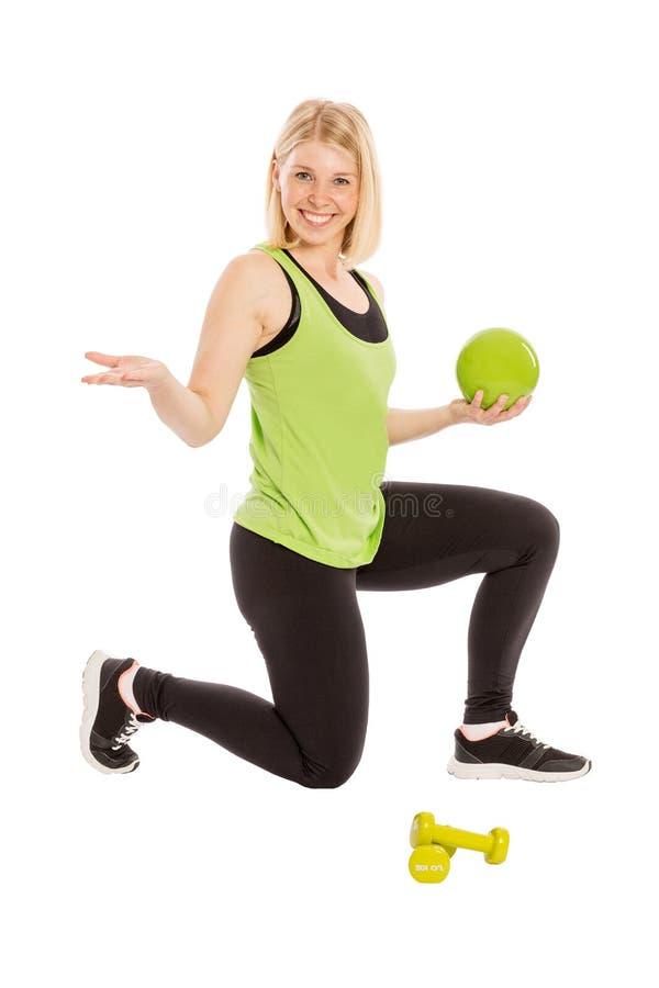 明亮的运动服的美丽的少妇有球和dumbbel的 免版税库存照片