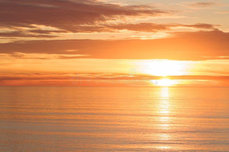 明亮的金黄剧烈的日落太阳反射的桔子,金子,镇静海洋 免版税库存图片