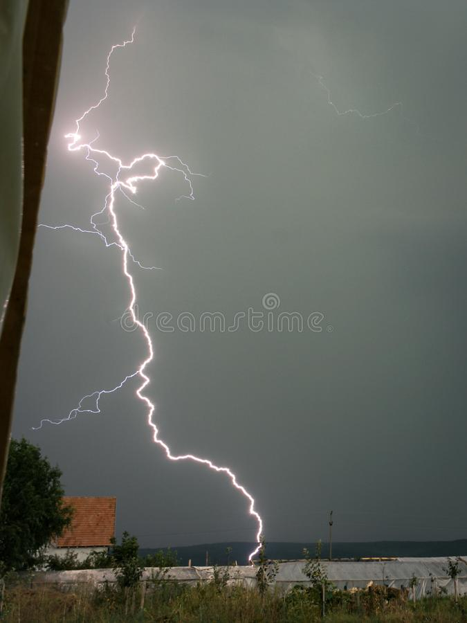 明亮的雷电在罗马尼亚碰撞非常接近一些间温室 免版税库存图片
