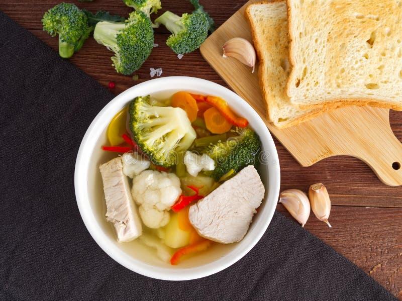 明亮的饮食汤用火鸡肉、花椰菜和菜,在棕色木背景,顶视图的未加工的硬花甘蓝 库存图片