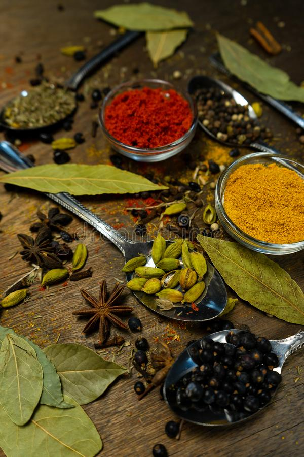 明亮的香料用咖哩粉调制胡椒豆蔻果实丁香在透明奶油的番红花肉豆蔻在木背景 免版税库存照片
