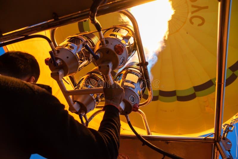明亮的黄色热空气气球飞行用煤气取暖器火焰由飞行员的热设备在卡帕多细亚,从里边低角度视图 免版税图库摄影
