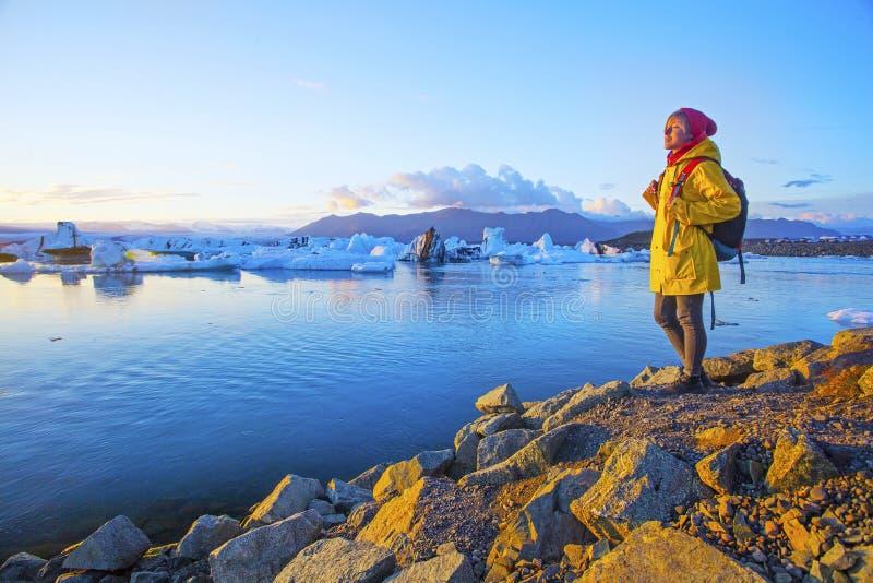 明亮的黄色雨衣的妇女在冰川盐水湖附近 免版税库存照片