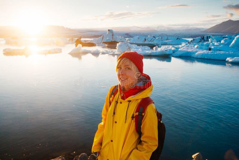 明亮的黄色雨衣的妇女在冰川盐水湖附近 免版税库存图片