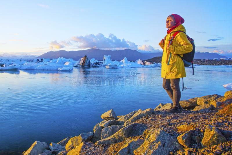 明亮的黄色雨衣的妇女在冰川盐水湖附近 库存图片