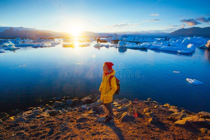 明亮的黄色雨衣的妇女在冰川盐水湖附近 免版税图库摄影