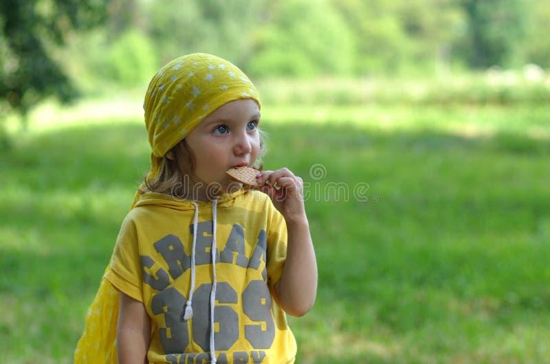 明亮的黄色方巾的一个小女孩吃饼干的 库存照片