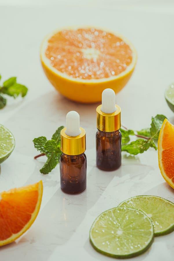 明亮背景中含有柠檬、橙、薄荷草提取物的有机化妆品 免版税库存照片