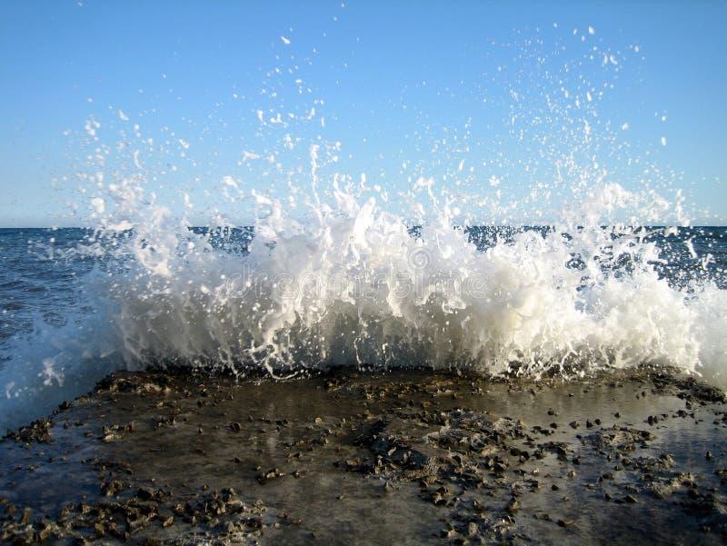 明亮飞溅海波浪在老石码头在一好日子 免版税库存照片