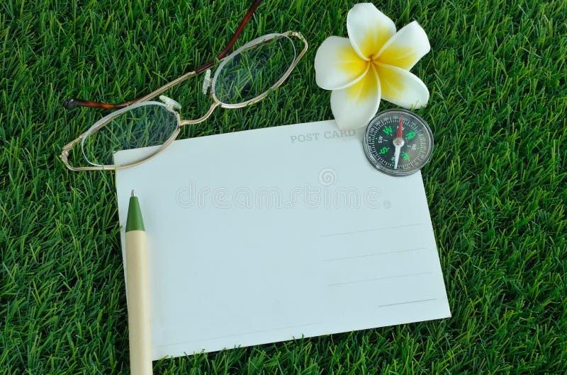 明信片、笔、玻璃、指南针和赤素馨花在草 免版税库存图片