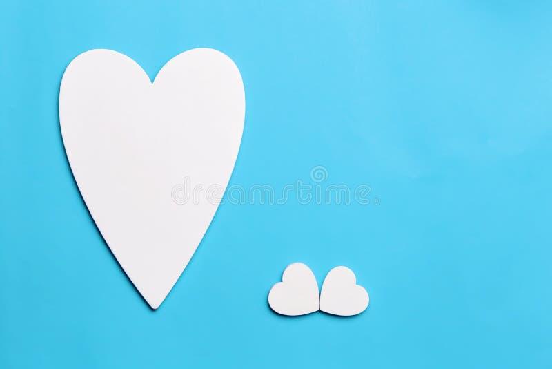 明信片对情人节,母亲节,与新出生的3月8日, 爱的标志是在天蓝色的白色木心脏 库存图片
