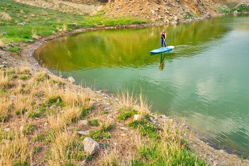 明轮轮叶一口的年轻女人在湖Iacobdeal,罗马尼亚,用浆划靠近海岸线,平静,原始水的,在日落 免版税库存照片