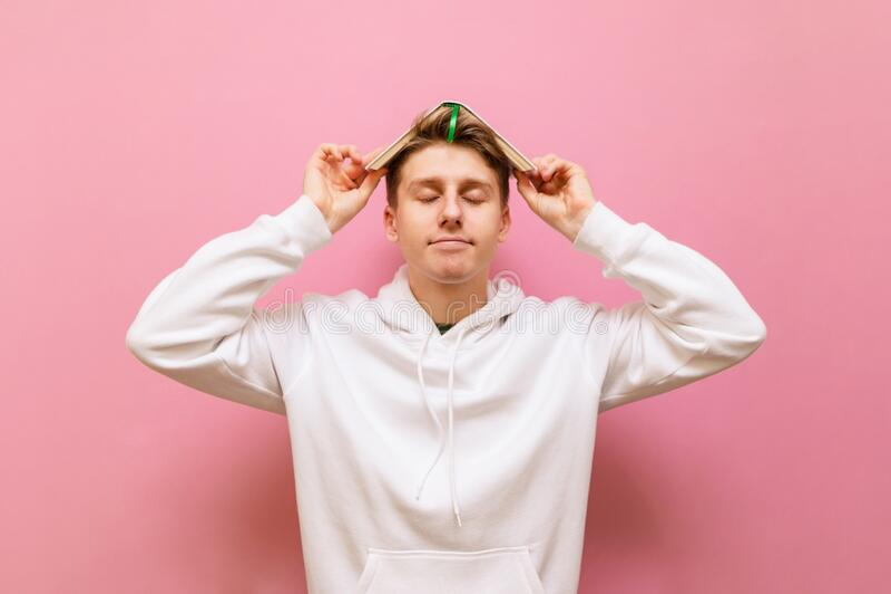昏昏欲睡的年轻学生,穿着粉红色背景上的白色休闲服,头顶上挂着书,微笑着 疲惫的画像 库存图片