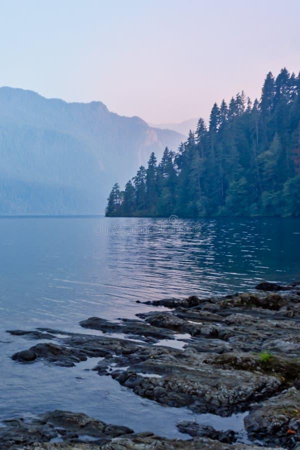 昏暗的日落垂直的射击在湖岸的 库存照片