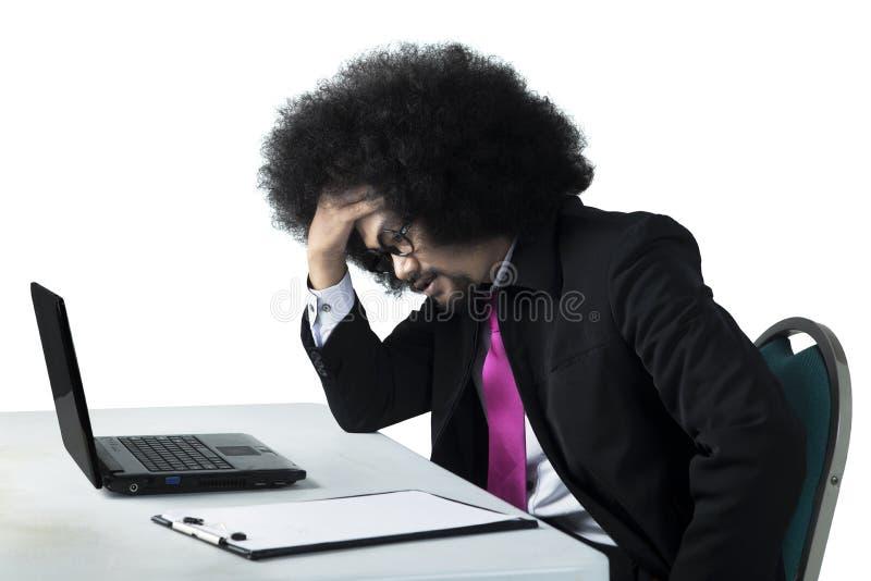 头昏眼花的蓬松卷发商人与膝上型计算机一起使用 库存图片