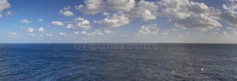 黄昏HDR一直跨过对天际和蓝色多云天空的海全景照片 库存图片