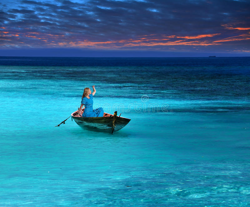 易碎的小船的美丽的妇女在风雨如磐的海看天际,盼望帮助 免版税库存照片