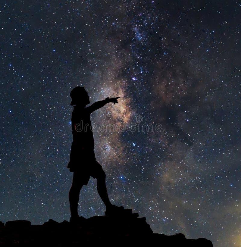 星俘获器 人在银河星系旁边站立 图库摄影