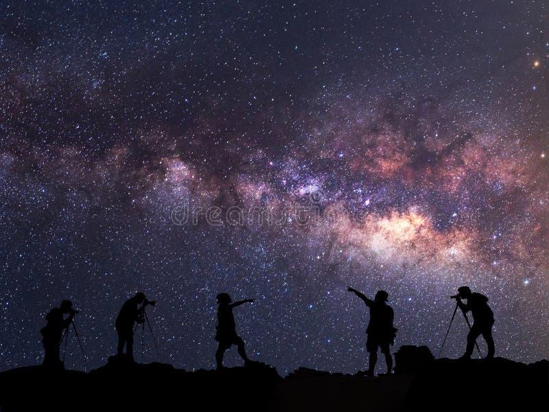 星俘获器 人在银河星系旁边站立 免版税库存照片