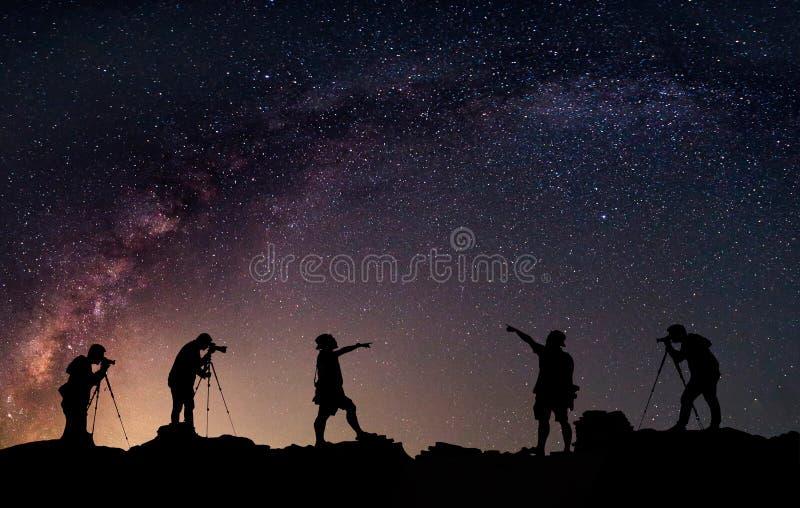 星俘获器 人在银河星系旁边站立 免版税库存图片