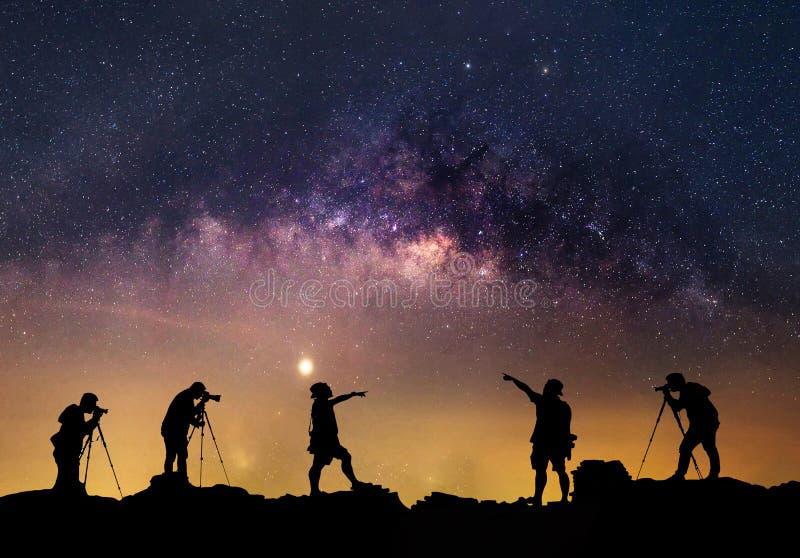 星俘获器 人在银河星系旁边站立 库存照片