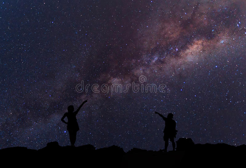 星俘获器 人在银河星系旁边站立 库存图片