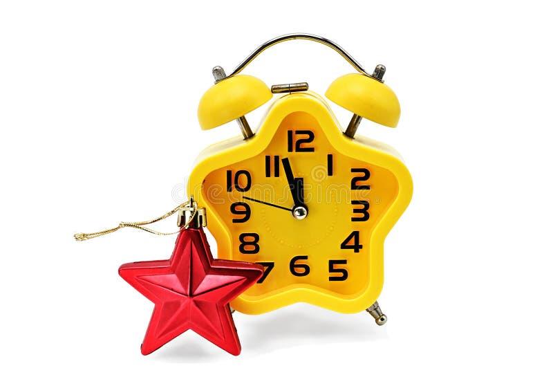 星号圣诞节时钟显示修理时间直到与红色星号的半夜12点,在白色背景 黄色 12,十二o 免版税库存图片
