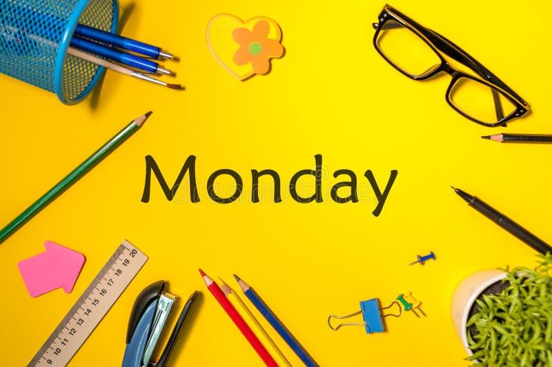 星期一 办公用品或学生成套装备在黄色桌上 企业创造性的概念,顶视图 免版税库存照片