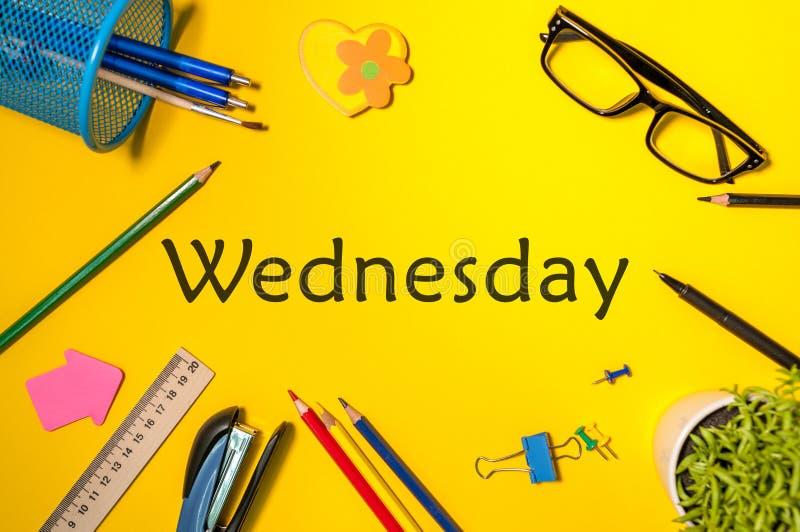 星期三 办公用品或学生成套装备在黄色桌上 企业创造性的概念,顶视图 免版税库存图片