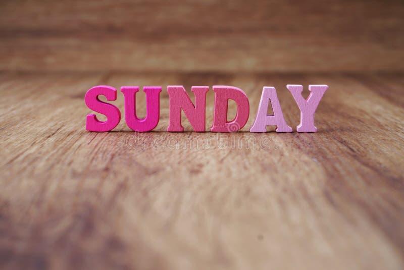星期天与空间拷贝的字母表信件在木背景 图库摄影
