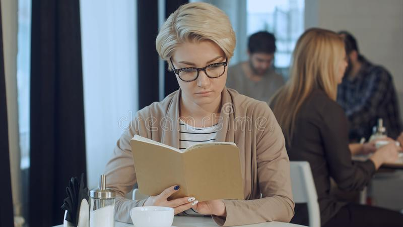 星期日早晨年轻行家妇女读书笔记生活方式场面关于她的笔记本的在咖啡馆 图库摄影