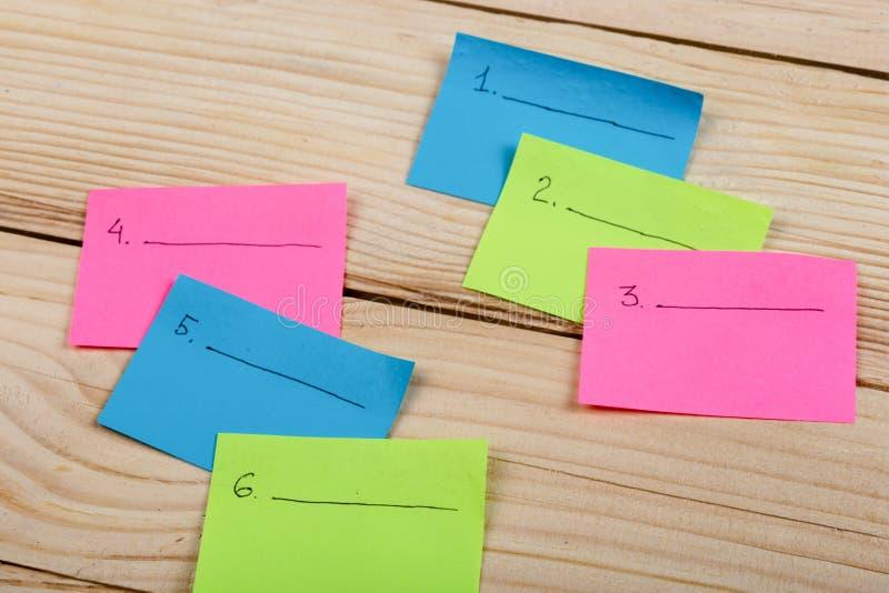 星期的计划在色的空白的贴纸的在木背景 免版税库存照片